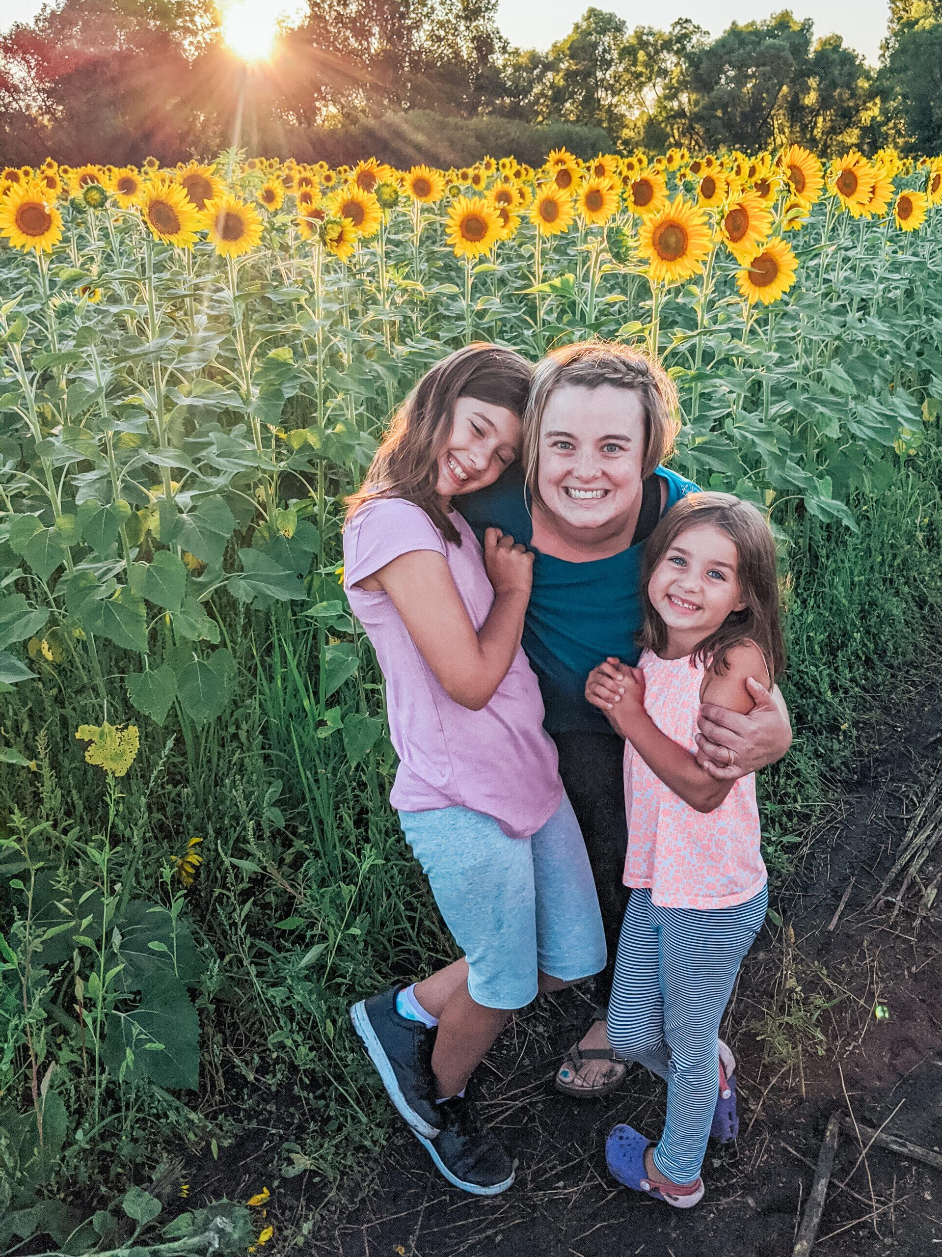Letting your child struggle - girls in field of sunflowers