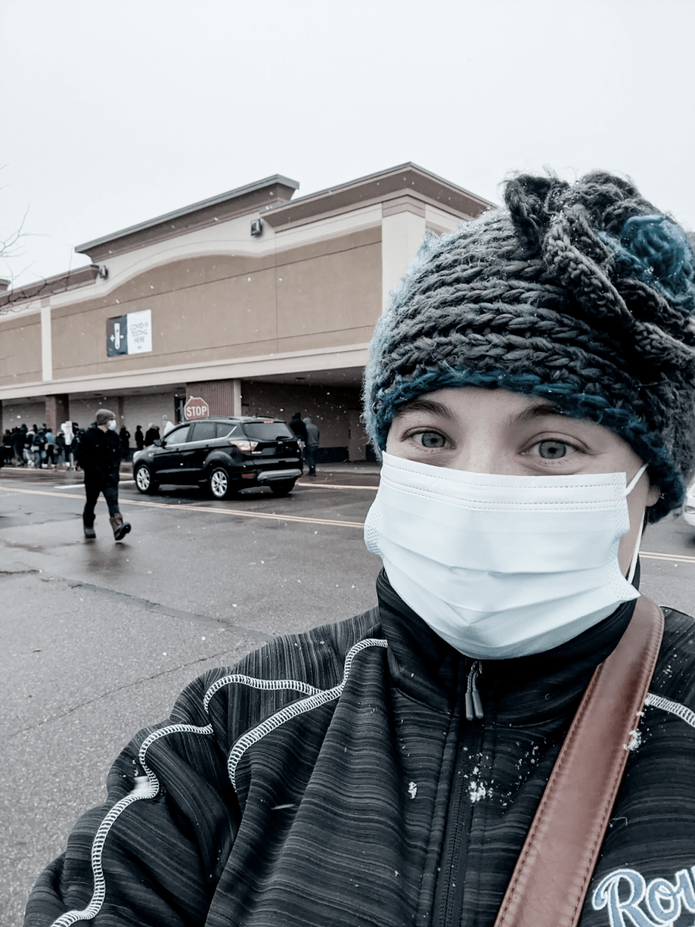 Woman standing with mask on at testing site. Mental illness and a pandemic