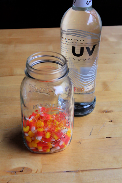 Mason jar of candy corn on table with vodka bottle.